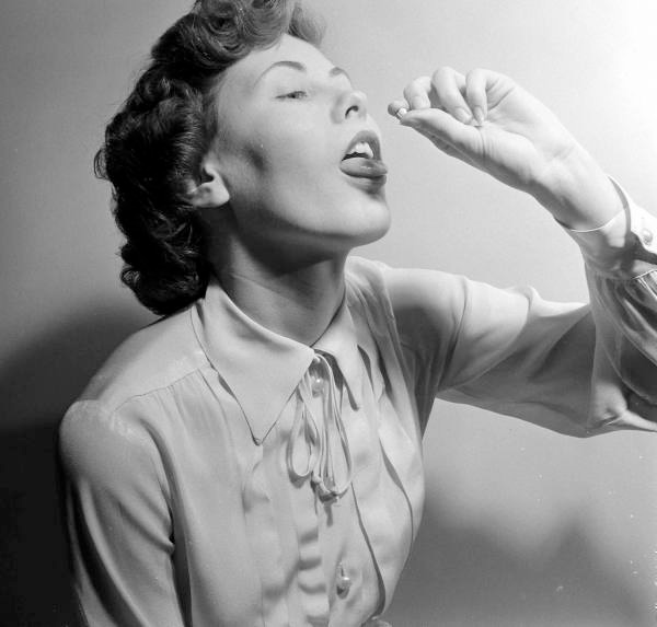 Funny pics~ vintage snap of woman taking a pill, 1950s