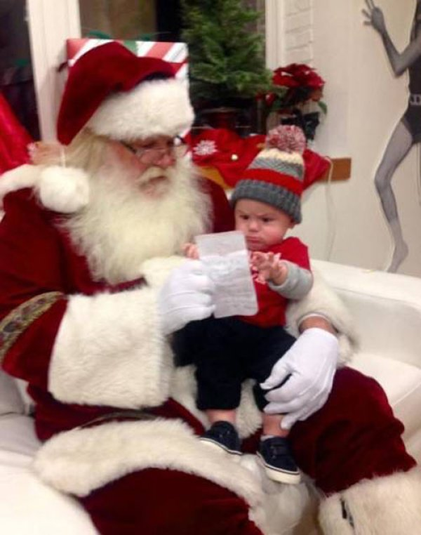 41 Funny Christmas Photos ~ baby not sure of Christmas list on Santa's lap