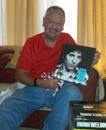Dan in December 2015, holding up an album of his favorite artist, Bruce Springsteen