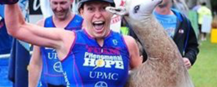 Vicki smiles as she crosses the finish line at Savageman with her Alpaca stuffed animal in tow