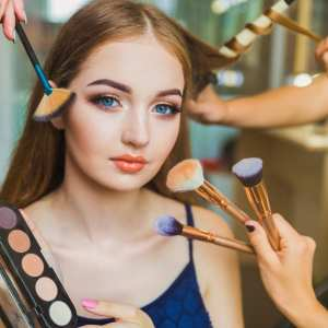 Portrait of the happy young woman who is sitting indoors and makeup artist doing makeup her and hairdresser doing the hairdo her