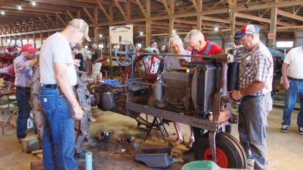 "Photo of Volunteers ""flash"" rebuilding the Farmall F-12"