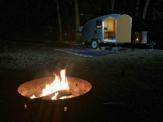 photo of a teardrop trailer and campfire