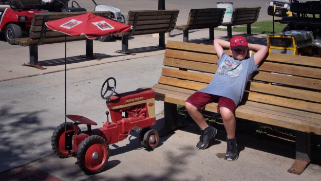 photo of boy with toy tractor resting on a bench
