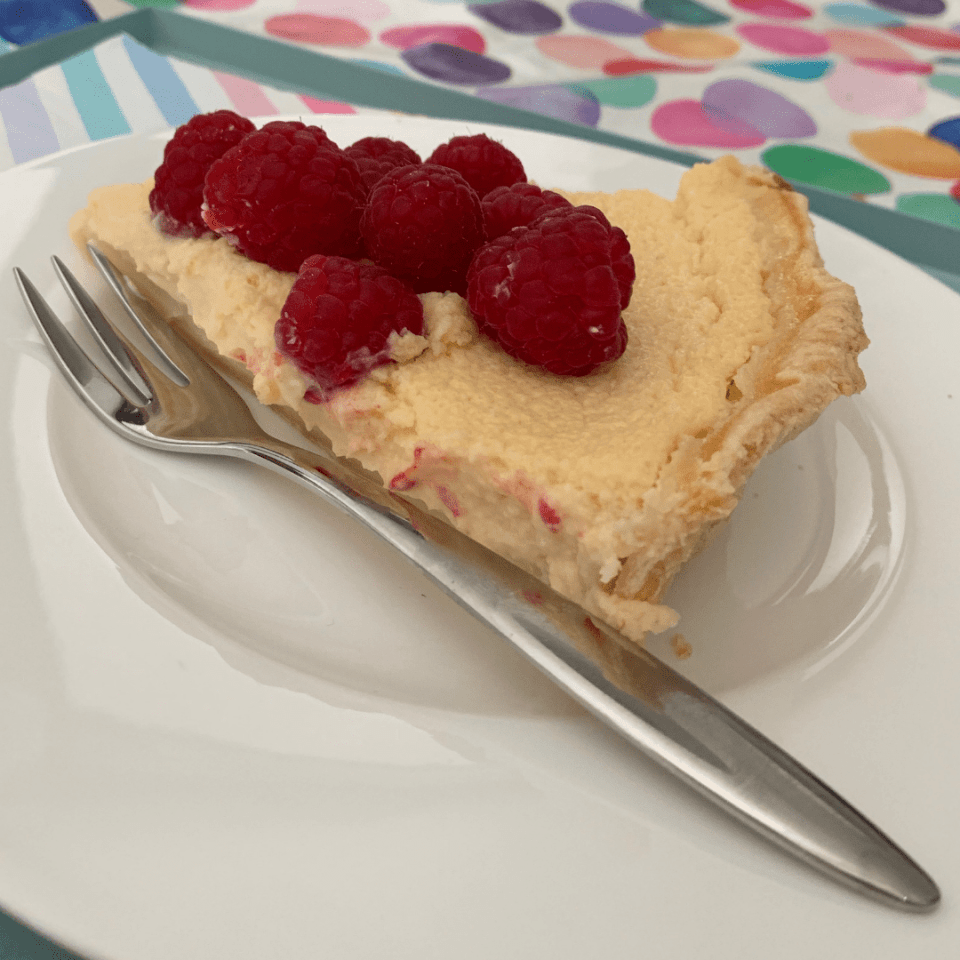 A slice of lime and raspberry tart on a white plate with a fork. Yum!