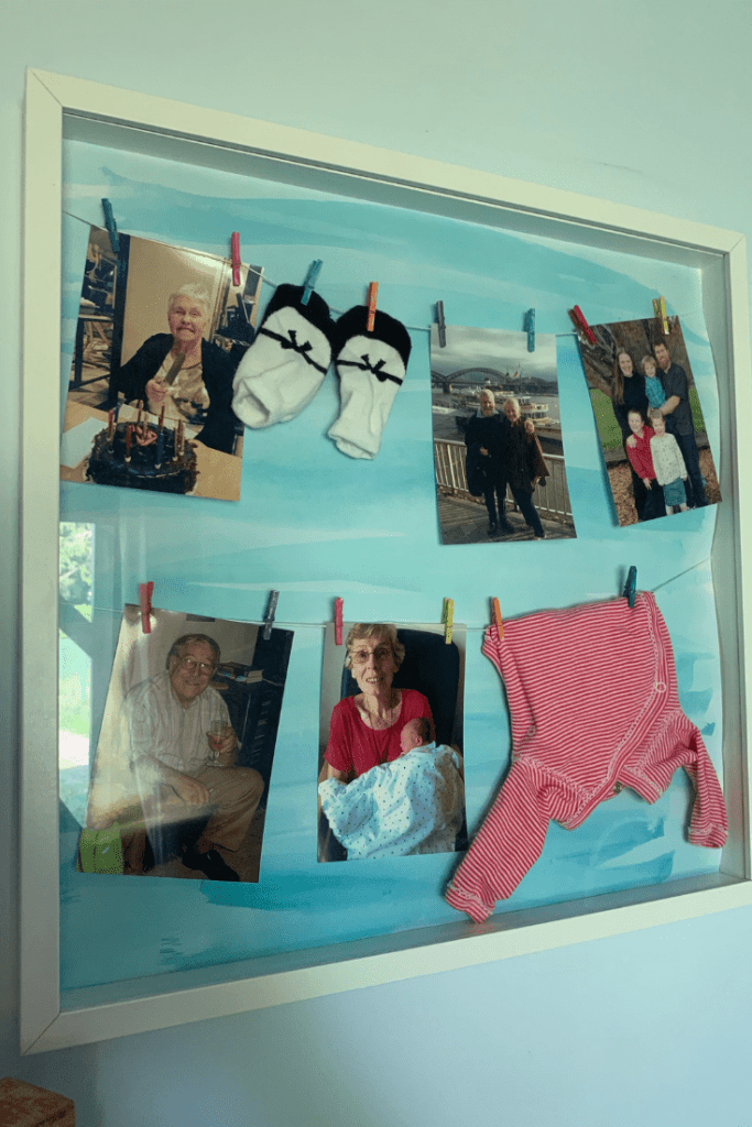 Clothes line wall art with photos and baby clothes
