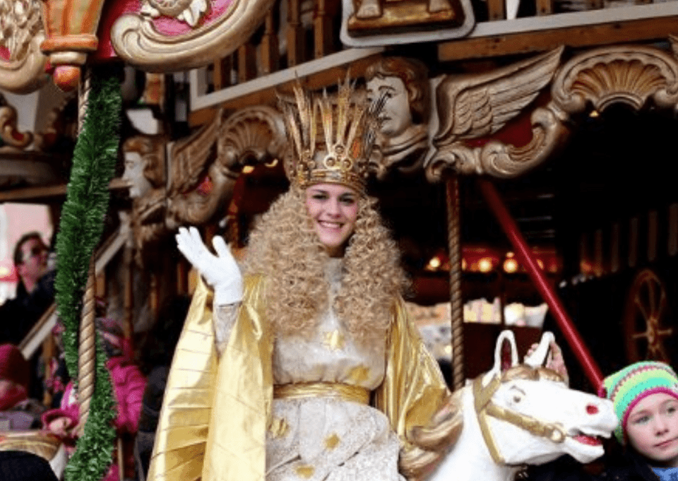 The 'Christkind' at the Nuremberg Christkindlmarkt, with her golden curls, large crown and gold dress and cape.