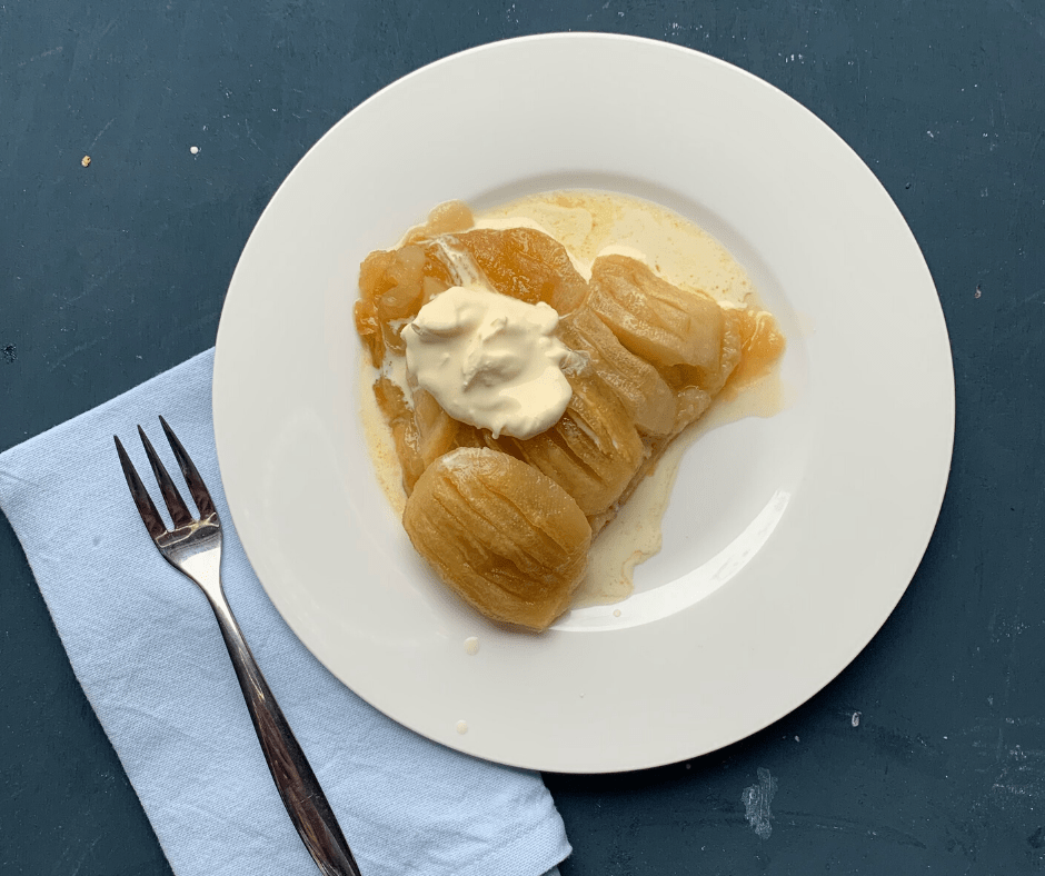 A slice of warm maple ginger tarte Tatin with cream, image includes blue serviette and fork