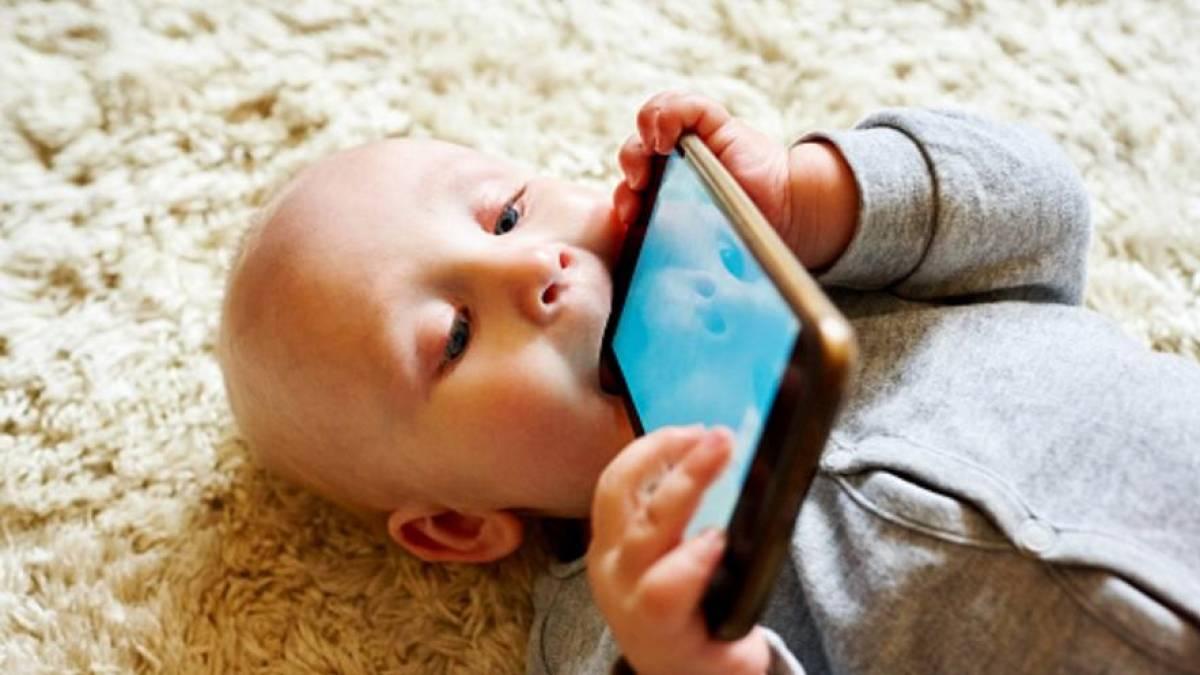 Criança com telefone na boca - Fonte: Pixabay