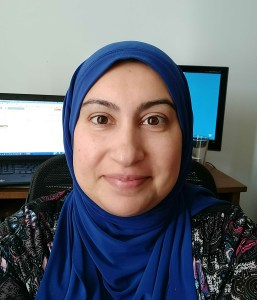 profile picture of muslim woman in tech, Sadiya Zackria. A smiling woman wearing hijab sitting in front of two computer monitors