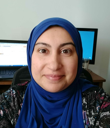 profile picture of Sadiya Zackria a smiling woman wearing hijab sitting in front of two computer monitors