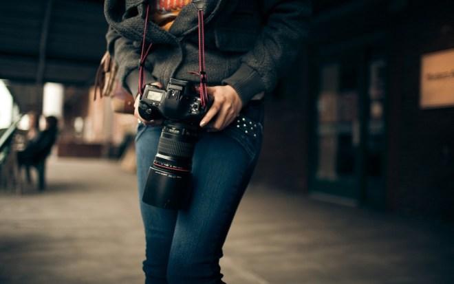 girl-holding-dslr-camera-denim-pants
