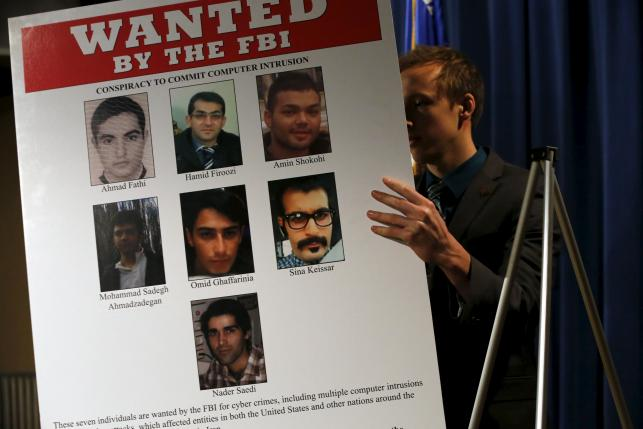 An aide unveils a wanted poster before Lynch and Comey hold a news conference to announce indictments on Iranian hackers at the Justice Department in Washington