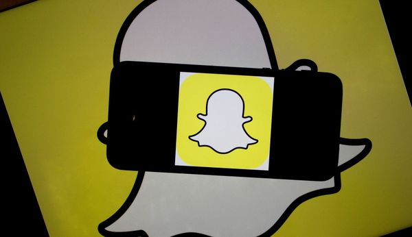 The Snapchat Inc. logo is displayed for a photograph on an Apple Inc. iPhone 5s and laptop computer in Washington, D.C., U.S., on Wednesday, Feb. 18, 2015. Snapchat Inc. is raising money that could value the company at as much as $19 billion. Photographer: Andrew Harrer/Bloomberg via Getty Images