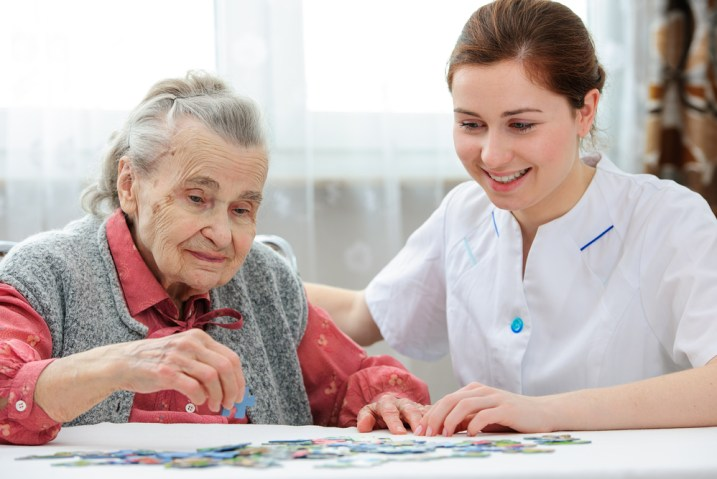 Woman living with dementia with care-giver playing with a jigsaw