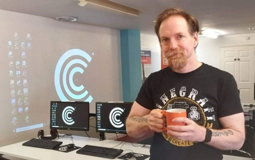 Man infront of a row of computers holding a mug