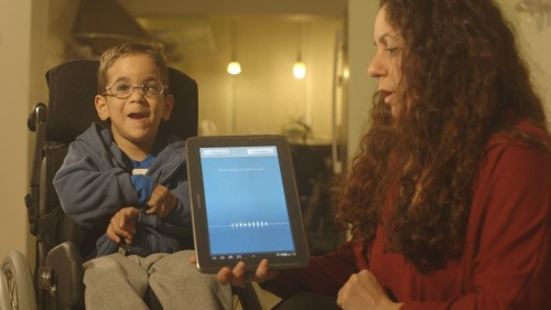 Woman holding tablet featuring Voiceitt app in front of young boy in a wheelchair