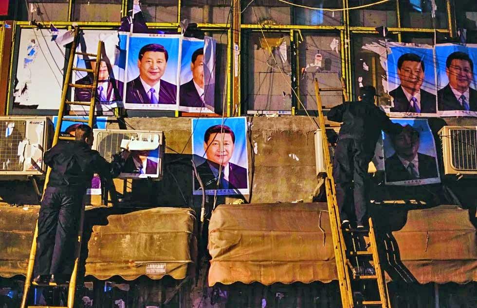 Chinese policemen taking down Xi Jinping posters