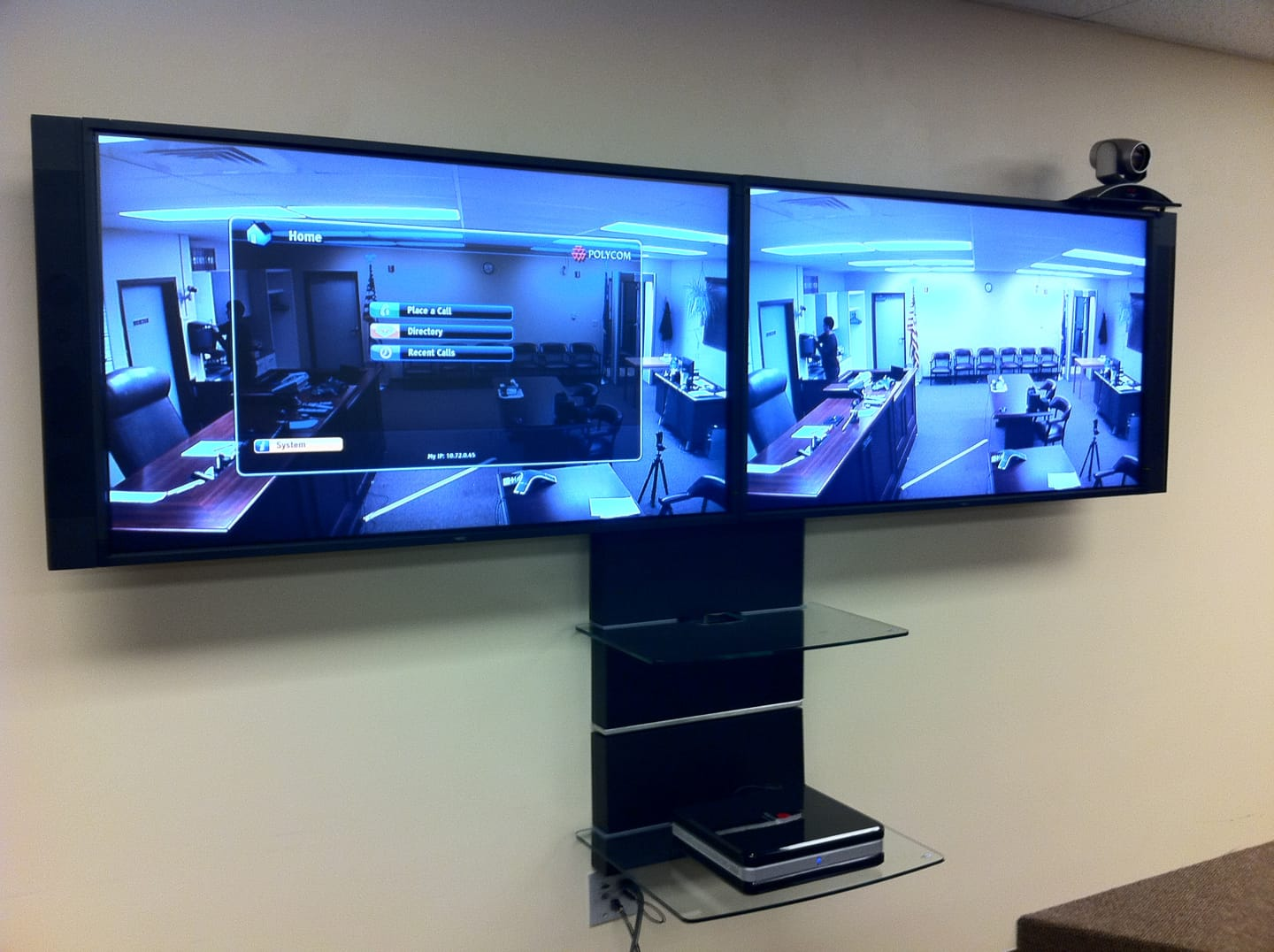 A Polycom VTC with dual 50 NEC monitors and a beautiful glass shelf system.