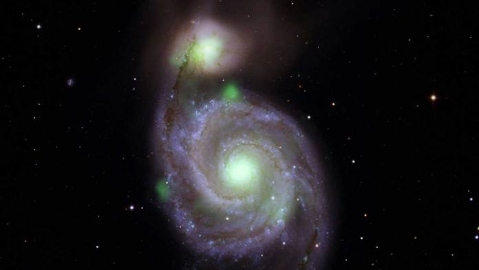 Bright green sources of high-energy X-ray light captured by NASA's NuSTAR mission are overlaid on an optical-light image of the Whirlpool galaxy (in the center of the image) and its companion galaxy, M51b (the bright greenish-white spot above the Whirlpool), taken by the Sloan Digital Sky Survey.Credit: NASA/JPL-Caltech, IPAC