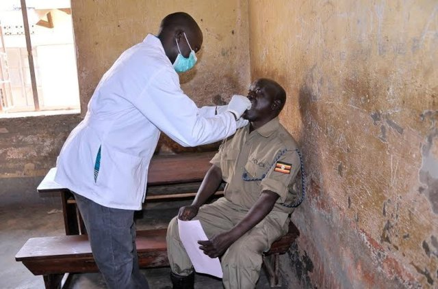 A police officer is attended to by a volunter dentist from Hind's Feet project at the Airtel community Health Fair In Arua District