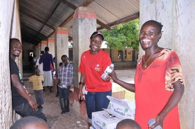 Airtel's Amanda sharing water with the residents that turned up for the Community health fair in Arua