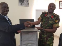 NITA-U's James Saaka hands over one of the laptops to Col. Ahimbisibwe