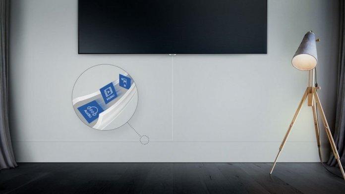 Durante décadas, el televisor ha sido un objeto estático, destinado a ubicarse en una sala o una habitación, y sin muchas posibilidades de moverse de un solo espacio para tratar de esconder la maraña de cables de la parte trasera. No obstante, hoy el televisor tiene la posibilidad de ser un dispositivo ágil y dinámico, con la opción de ubicarse en cualquier lugar y reubicarse cuando lo deseemos. Es así que Samsung logró que esos cables antiestéticos desaparecieran y se volvieran uno solo: el One Invisible Connection, eliminando el desorden, dándole un aspecto mucho más limpio al espacio donde coloquemos el televisor. El primero en su clase En el 2013, Samsung presentó la primera solución para la administración de cables llamada One Connect Box, la cual funcionaba como una pequeña caja o hub donde se le conectaban todos los dispositivos al televisor. Esta caja podía colocarse lejos del televisor, y/o esconderse, logrando mucha mayor estética al reducir la visibilidad de los cables. Sobre la base de ese desarrollo, en el 2017, la compañía mostró el Invisible Connection, un solo cable muy delgado que transmitía audio, video y datos. Este año, Samsung dio a conocer la evolución del One Invisible Connection: una nueva conexión invisible que integra todo, video, audio, datos y energía. Esta solución es el resultado de la constante escucha y preocupación de Samsung por sus consumidores, así como de apostar siempre por la innovación. Este año, mientras se desarrollaba la nueva versión, la empresa llegó a la conclusión de que las personas torcían y moldeaban los cables para ocultar una el de corriente. Tomando esto en cuenta, se logró integrar todo en un solo cable, algo que sin duda se vuelve fundamental para aumentar la libertad que se necesita para ubicar el TV. De este modo, los televisores QLED 2018 de Samsung se liberaron de las restricciones, pues con el One Invisible Connection de 5 metros de largo, conectado al One Connect, pueden ser colocados en cualquier lugar, e