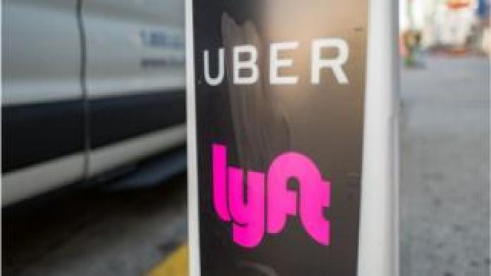 Uber and Lyft logos by a taxi