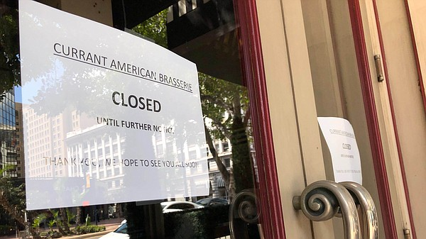 A closed sign at the Currant American Brasserie in downto...