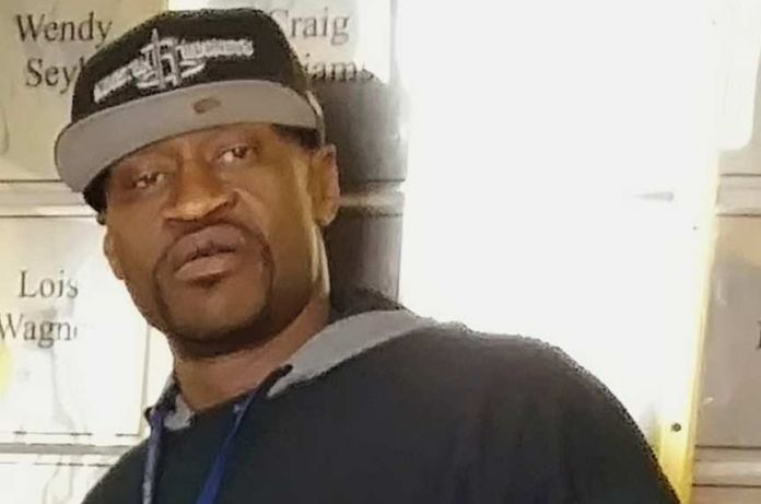 An African American man in a cap and a t-shirt with security written across it