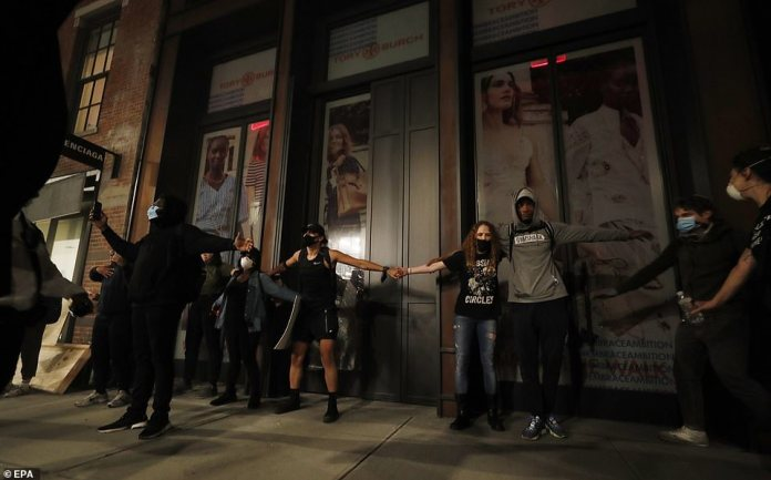 Peaceful protesters pictured making a chain with their arms to block looters from entering this closed Tory Burch store on Sunday evening amid growing civil unrest