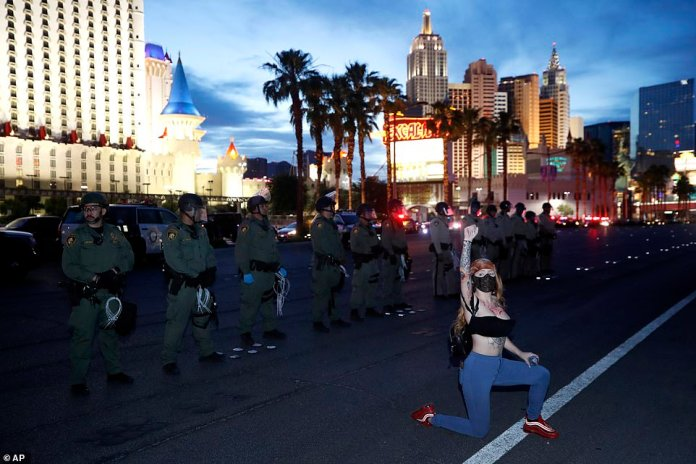 A woman protests in front of a line of Las Vegas Police officers on the Las Vegas Strip on Sunday