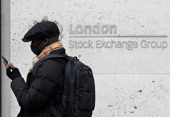 © Reuters. FILE PHOTO: A man wearing a protective face mask walks past the London Stock Exchange Group building in the City of London financial district, whilst British stocks tumble as investors fear that the coronavirus outbreak could stall the global economy, in