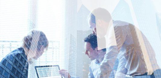 Drei Menschen vor einem kleinen PC Monitor vor Fenster mit Jalousien, transparentes Overlay von Hochhausfronten