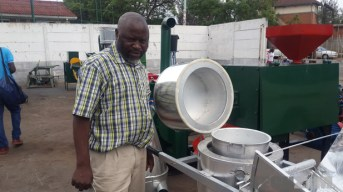 Solomon Marimo stands next to his solar stove