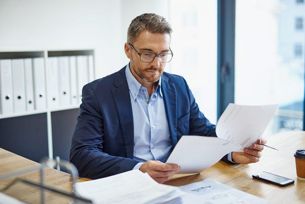 Imagem mostra homem lendo documentos