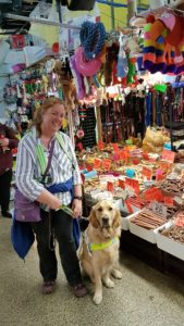 Ma and Teddy posing in front of the huge pet supplies stall in Birmignham's Rag Market. Behind them is an enormous array of dog chews and treats