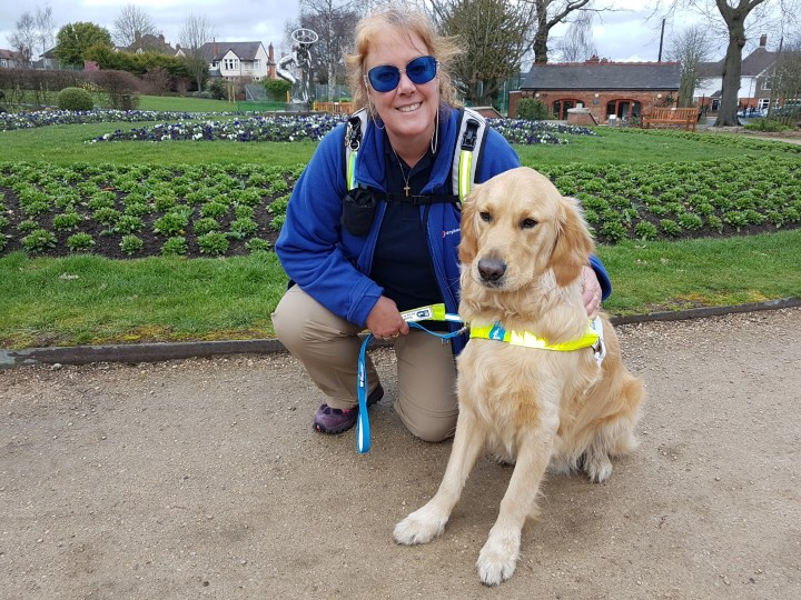 Ma kneeling down next to Teddy, who is in his white Guide Dog harness with yellow chest band. They are on a concrete path with grass and flower beds behind.
