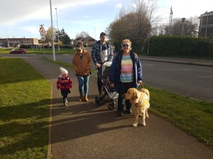 Teddy leading the way, guiding Mummy on a pavement beside a grass verge, with James and Rosie walking behind. Rosie has Hallie (almost 3) walking beside her and James is 'wearing' baby Theo in a babywrap on his front
