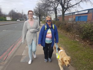 Teddy working in harness guiding Mummy along a pavement with grass beside it. Mummy is wearing a mid blue open fleece jacket and rainbow striped jumper and black trousers. Beside her is Debbi - tall and slim wearing pale jeans and grey cardigan wrapped around her