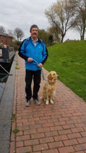 Daddy wearing blue fleece jacket and black trousers, standing on brick-surfaced towpath with wide expanse of grass to the RHS of picture. Teddy is in a sit beside him gazing off across the grass