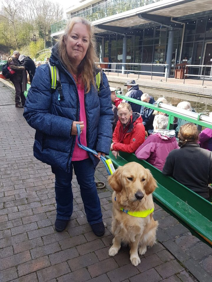 Teddy in a sit, in harness, with Mummy standing beside him. Behind them is the open-topped green narrowboat from which they have just disembarked. Most of the rest of the passengers on the tripboat are still aboard, but have removed their hardhats ready to disembark