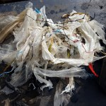 A large pile of shredded sheet plastic and twigs, plus various other bits of detritus piled on the dark blue back deck of the boat