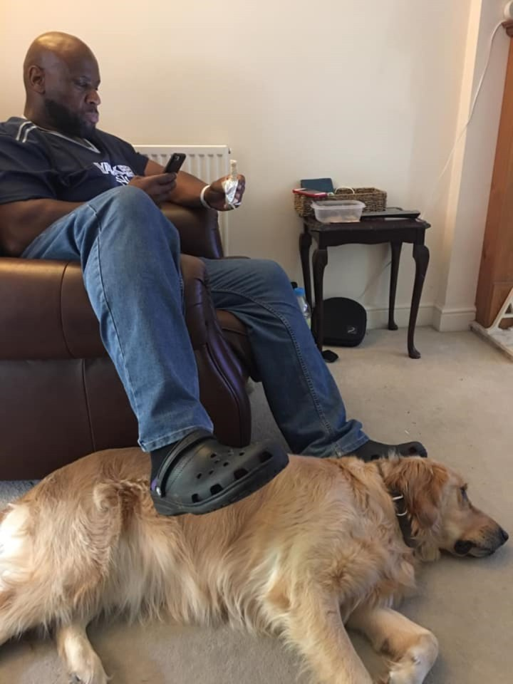 Teddy lying on his side on cream carpet beside DaddyJon who is sitting in a brown leather armchair with his leg dangling over the arm above Teddy