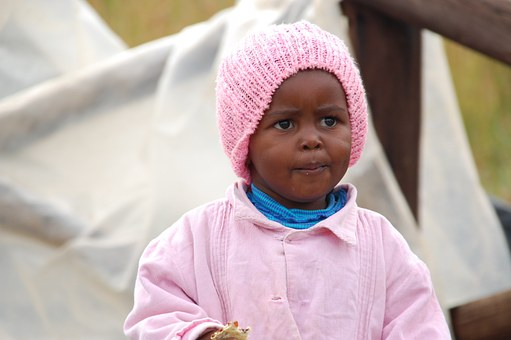 black kid with a pink bonnet and jacket