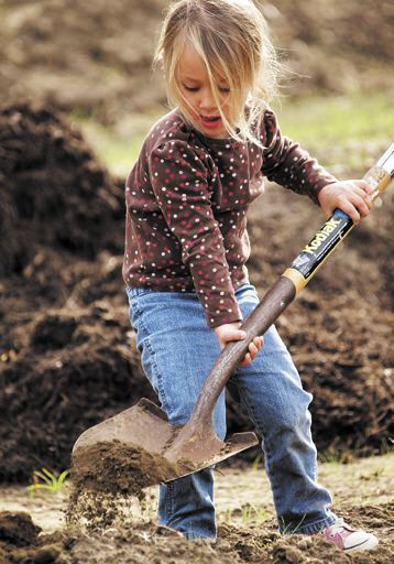 Happy to help out, Ellamae McKinney, 3, digs a hole where a tree will be planted at Mesa Harmony Garden.