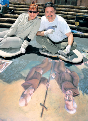 Featured artists at this year's I Madonnari are Wayne and Cheryl Renshaw. The artists have been preparing their chalk works for the opening of the festival today. MIKE ELIASON/NEWS-PRESS