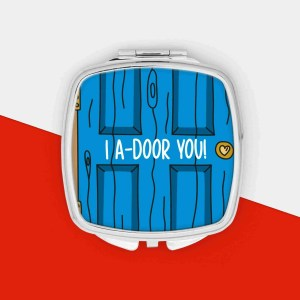 """Blue and silver pocket mirror with door illustration and the phrase """"I A-Door You"""" on the front."""