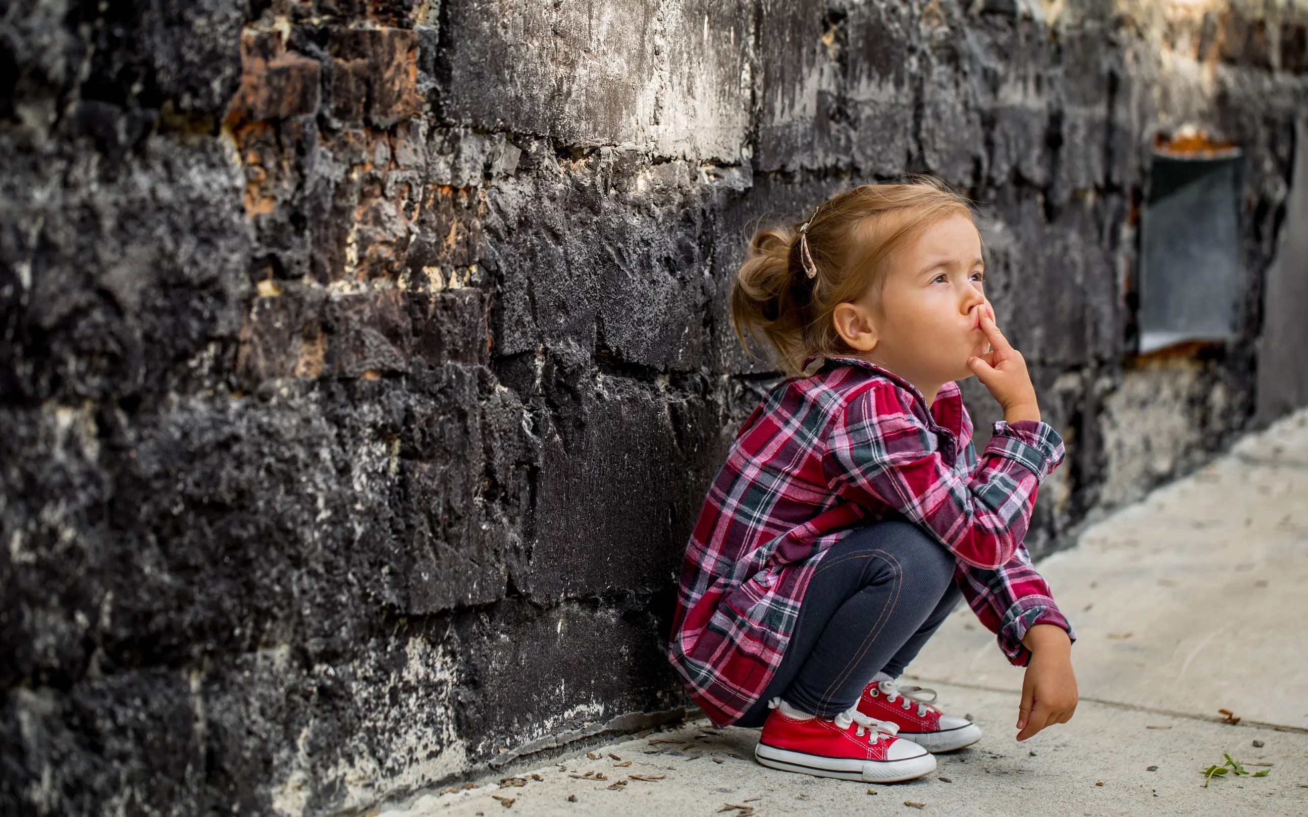 child crouching on wall